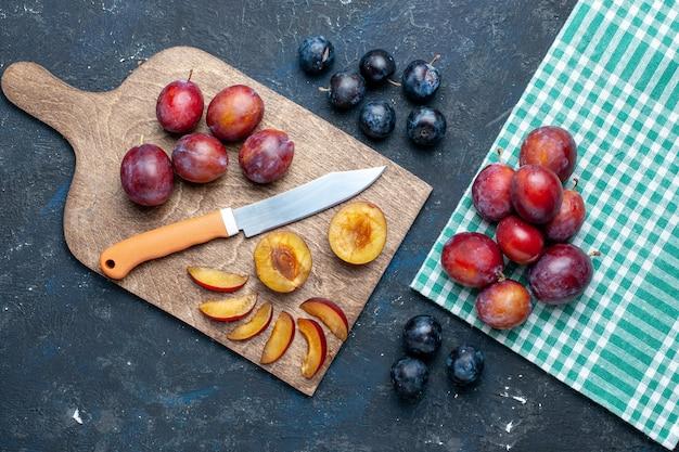 Vista superior de ameixas frescas inteiras maduras e suculentas cortadas em uma mesa escura, frutas com vitaminas frescas no verão