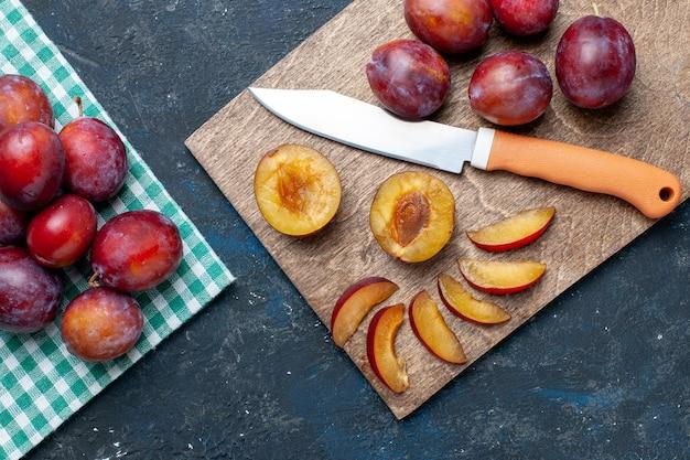 Vista superior de ameixas frescas inteiras maduras e suculentas em uma mesa cinza-escuro, frutas com vitaminas frescas no verão