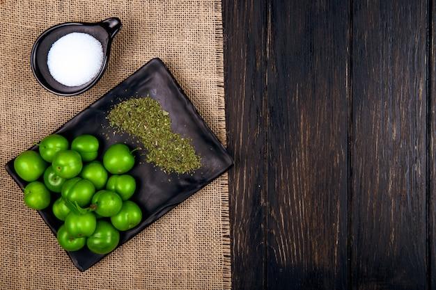 Vista superior de ameixas verdes azedas com hortelã-pimenta seca em uma bandeja preta e sal de saco na mesa de madeira escura com espaço de cópia