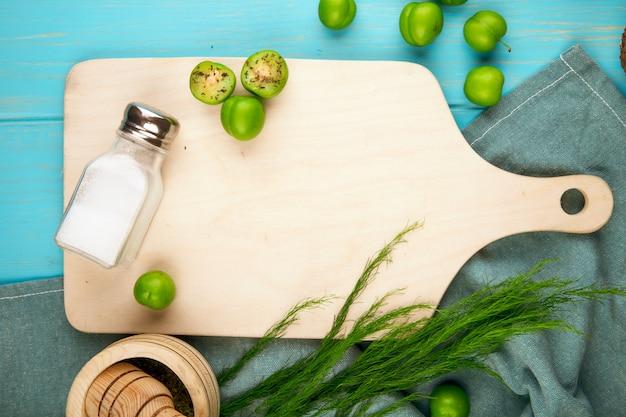 Vista superior de ameixas verdes azedas e um saleiro em uma tábua de madeira com espargos na mesa azul