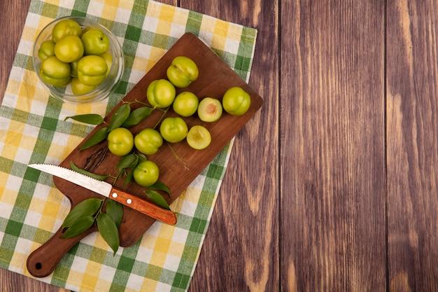 Vista superior de ameixas verdes com faca e folhas em uma tábua e frasco de ameixas em tecido xadrez e fundo de madeira com espaço de cópia