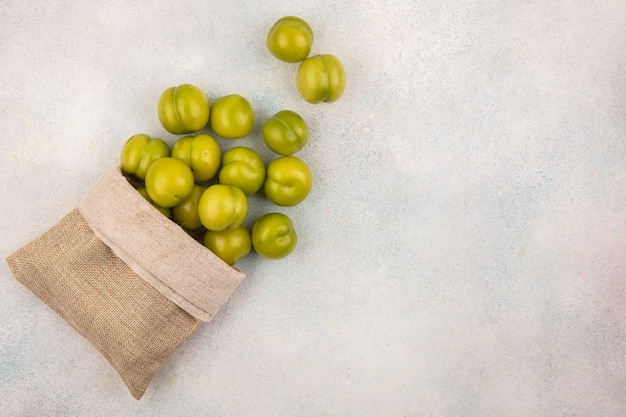 Vista superior de ameixas verdes derramando do saco no fundo branco com espaço de cópia
