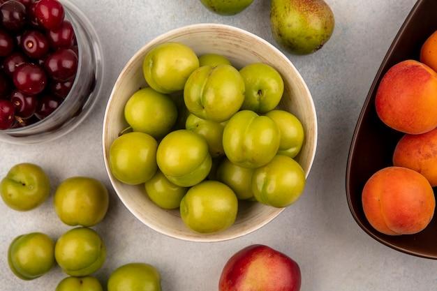 Vista superior de ameixas verdes em uma tigela e um frasco de cerejas em uma tigela de damascos com pêra e pêssego no fundo branco