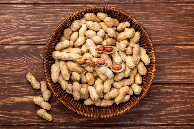 Vista superior de amendoim com casca em uma cesta em uma mesa de madeira