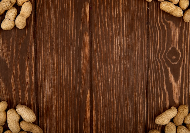 Vista superior de amendoins com casca espalhados sobre fundo de madeira com espaço de cópia