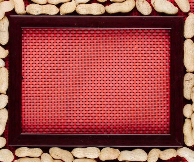 Vista superior de amendoins em casca, dispostos em torno da moldura vazia sobre fundo vermelho, com espaço de cópia