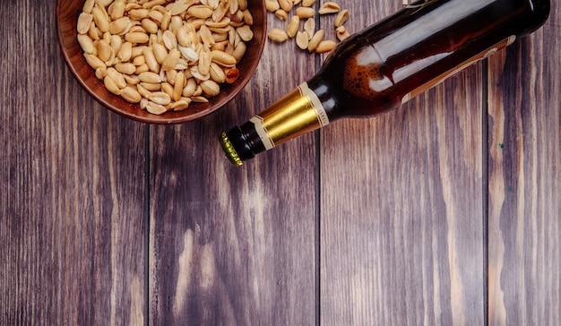 Vista superior de amendoins em uma tigela de madeira com uma garrafa de cerveja no rústico, com espaço de cópia