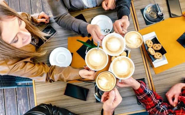 Vista superior de amigos brindando cappuccino em restaurante cafeteria