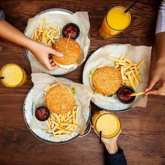 Vista superior de amigos comendo hambúrgueres com batatas fritas