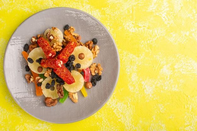 Vista superior de anéis de abacaxi junto com frutas secas e torrão dentro do prato