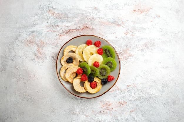 Vista superior de anéis de abacaxi secos com kiwis secos e maçãs na superfície branca