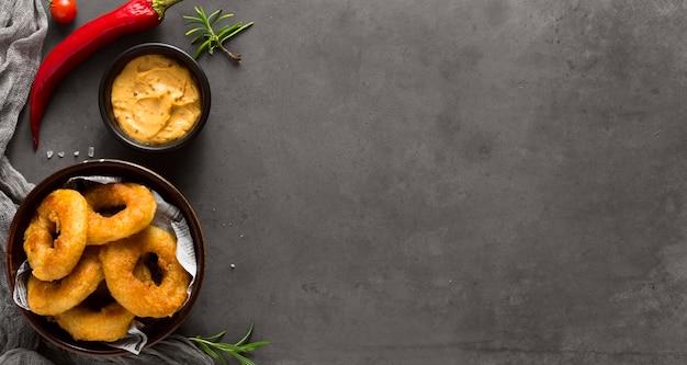 Vista superior de anéis de batata frita com mostarda e pimenta malagueta