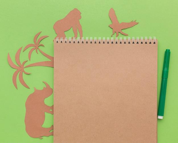 Vista superior de animais de papel com caderno e caneta para o dia animal
