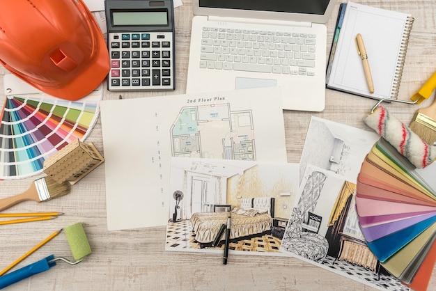Vista superior de arquitetos desenhando uma casa moderna com material de amostra, capacete de segurança, laptop na mesa criativa