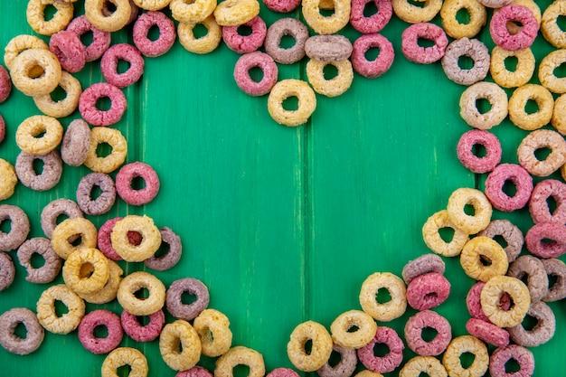 Vista superior de arranjos em forma de coração de cereais coloridos na superfície verde