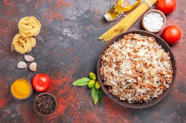 Vista superior de arroz cozido com massa crua e tomate na foto de comida de refeição escura de prato de superfície escura