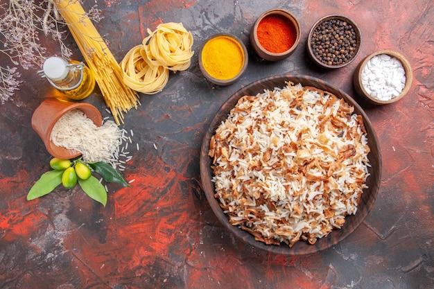 Vista superior de arroz cozido com temperos em um prato de refeição fotográfica escura de mesa