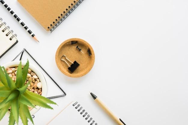 Vista superior de artigos de papelaria de escritório com cadernos e suculentas