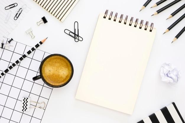 Vista superior de artigos de papelaria de escritório com café e notebook