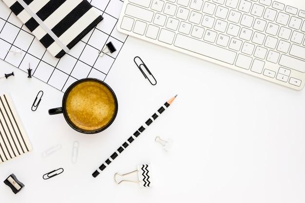 Vista superior de artigos de papelaria de escritório com café e teclado