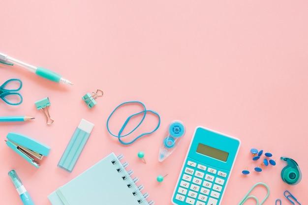 Vista superior de artigos de papelaria de escritório com calculadora e faixas elásticas