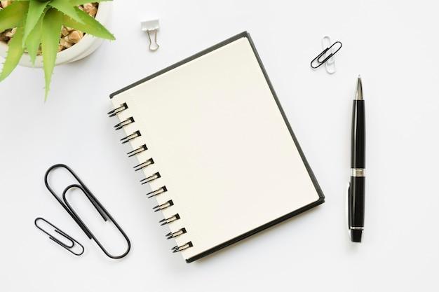 Vista superior de artigos de papelaria de escritório com clipes de papel e caderno