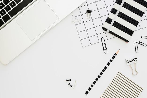 Vista superior de artigos de papelaria de escritório com laptop e clipes de papel