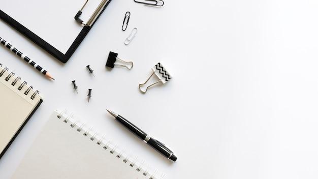 Vista superior de artigos de papelaria de escritório com notebook e clipes de papel