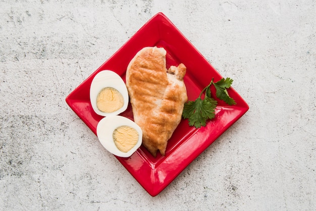 Vista superior, de, assado, asas galinha, com, ovo fervido, em, prato vermelho, sobre, concreto, chão