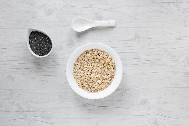 Vista superior de aveia; sementes de chia e colher contra a mesa de madeira