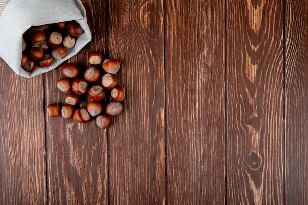 Vista superior de avelãs com casca espalhadas de um saco em fundo de madeira com espaço de cópia