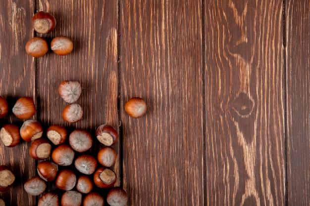 Vista superior de avelãs com casca espalhadas sobre fundo de madeira com espaço de cópia