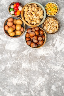 Vista superior de avelãs e amendoins com doces na superfície branca