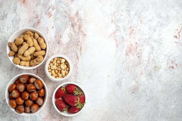Vista superior de avelãs e amendoins com morangos na superfície branca
