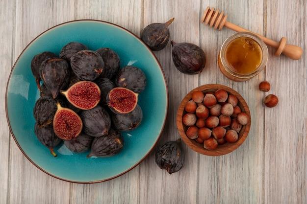 Vista superior de avelãs em uma tigela de madeira com figos maduros pretos em um prato azul com mel em uma jarra de vidro e uma colher de mel em uma parede de madeira cinza