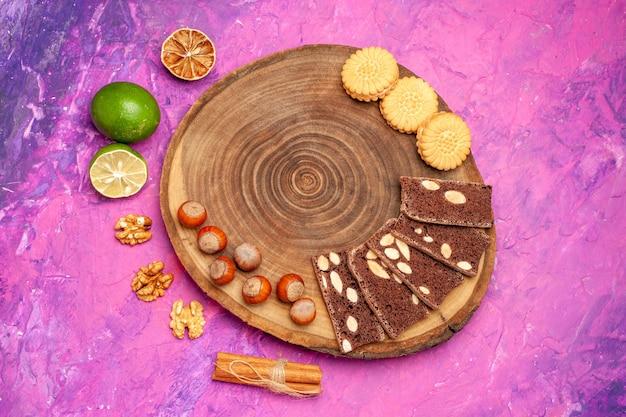 Vista superior de avelãs frescas com biscoitos e bolo na superfície rosa