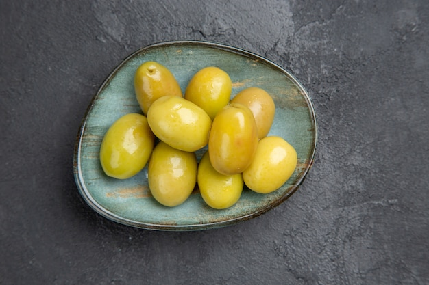 Vista superior de azeitonas verdes orgânicas frescas em um prato azul em um fundo escuro
