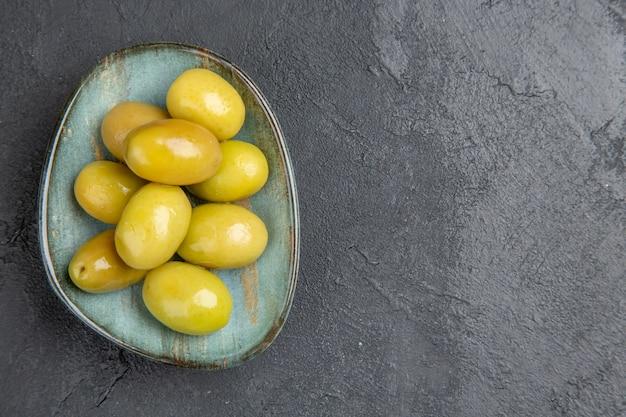 Vista superior de azeitonas verdes orgânicas frescas em um prato azul no lado direito em um fundo escuro
