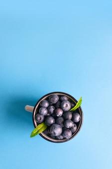 Vista superior de bagas de mirtilo maduras frescas com hortelã em uma caneca de metal sobre uma superfície azul