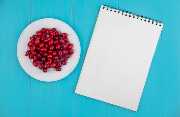 Vista superior de bagas vermelhas frescas de cornel em um prato branco sobre um fundo azul de madeira com espaço de cópia