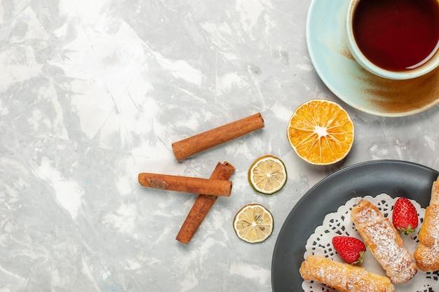 Vista superior de bagels de açúcar em pó com morangos, canela e xícara de chá na mesa branca