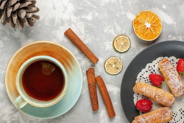 Vista superior de bagels de açúcar em pó com morangos e uma xícara de chá na superfície branca