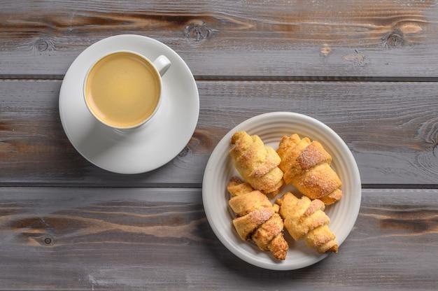 Vista superior de bagels de biscoitos caseiros e café na superfície de madeira