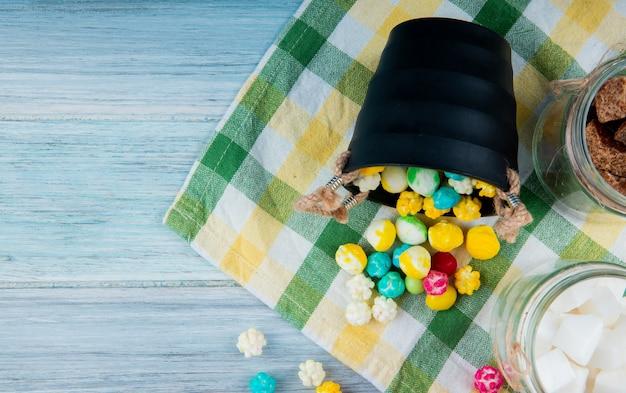 Vista superior de balas de açúcar coloridas espalhadas de um balde no guardanapo de mesa xadrez em fundo rústico, com espaço de cópia