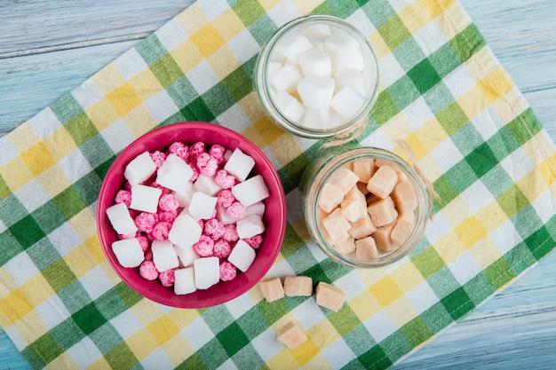 Vista superior de balas de açúcar rosa em uma tigela e diferentes tipos de açúcar em potes de vidro guardanapo de mesa xadrez em fundo rústico