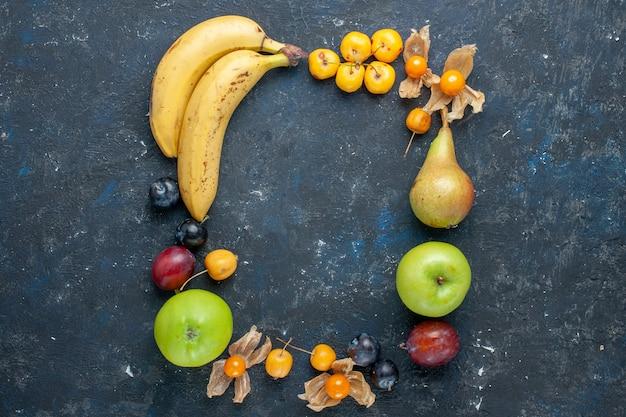 Vista superior de bananas amarelas com maçãs verdes frescas, peras, ameixas e cerejas doces na mesa escura, frutas com vitaminas saudáveis e baga