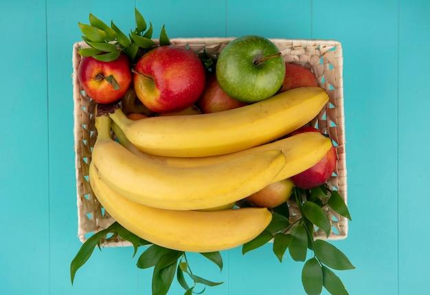 Vista superior de bananas com maçãs coloridas e pêssego em uma cesta com galhos em uma superfície turquesa