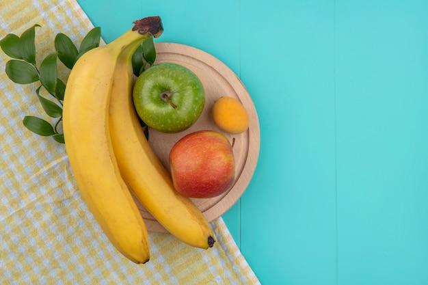 Vista superior de bananas com maçãs em um suporte em uma toalha amarela quadriculada em uma superfície azul