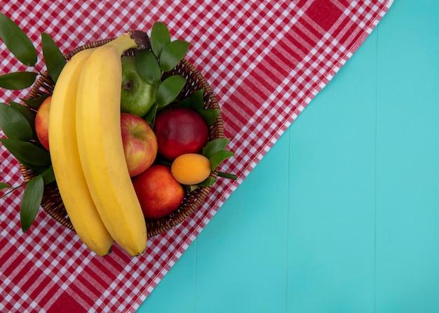 Vista superior de bananas com pêssegos e maçãs em uma cesta em uma toalha quadriculada vermelha em uma superfície azul