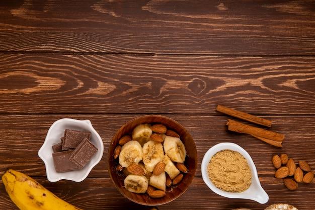 Vista superior de bananas fatiadas com amêndoa em uma tigela de madeira, chocolate escuro e paus de canela na madeira rústica, com espaço de cópia